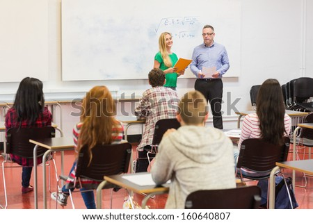 Rear view of students attentively listening to female by teacher in the classroom - stock photo