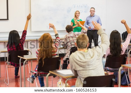 Rear view of students with hands raised in the classroom - stock photo