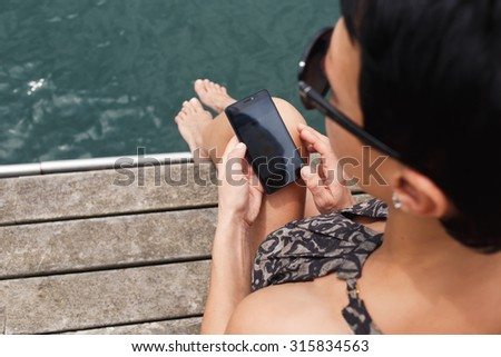 Rear view of stylish woman holding cell telephone with copy space area for your text message or advertising content, female chatting on her mobile phone while relaxing on a wooden pier against water - stock photo