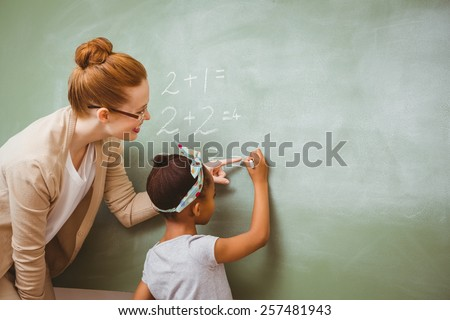 Rear view of teacher assisting little girl to write on blackboard in the classroom - stock photo