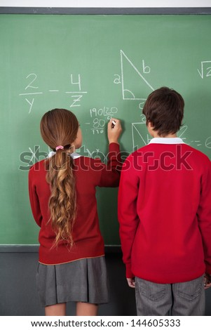 Rear view of teenage students solving mathematics on board in classroom - stock photo