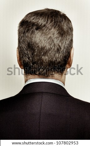 Rear view of the back of a man's head and shoulders. The man is middle aged with graying hair. Background is a stripy wall paper. - stock photo