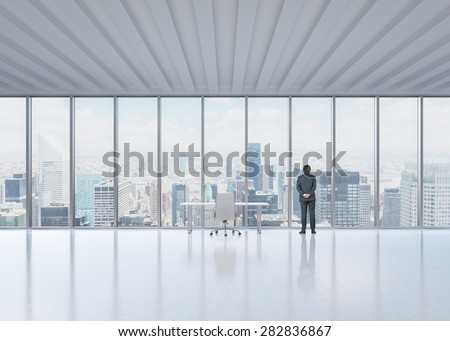 Rear view of the businessman who looks out the window in New York's panoramic office. A concept of the modern workplace. - stock photo
