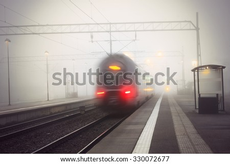 Rear view of train leaving station on foggy gloomy day - stock photo