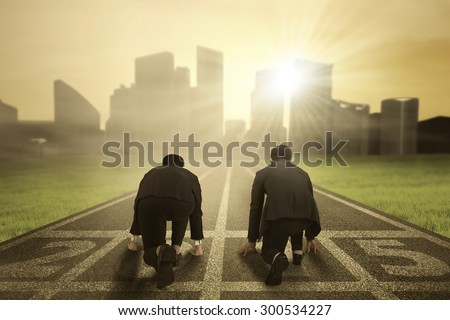 Rear view of two businessmen ready to compete on the track with number 2015 - stock photo