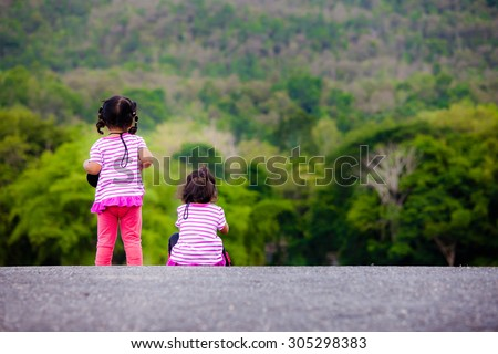 Rear view of two little girl at park - stock photo