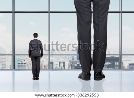 Rear view of two professionals in formal suites who stand in front of panoramic window with New York city view. The concept of professional consulting services. - stock photo