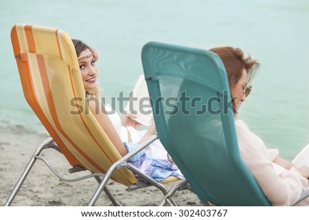 Rear view of two young woman reading books while relaxing on the beach  - stock photo