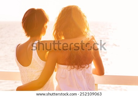 Rear View Of Two Young Women Looking At Sea At Sunset - stock photo