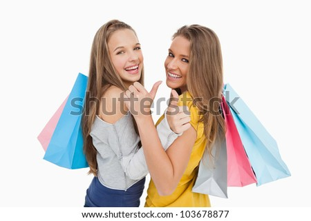 Rear view of two young women the thumb-up with shopping bags against white background - stock photo