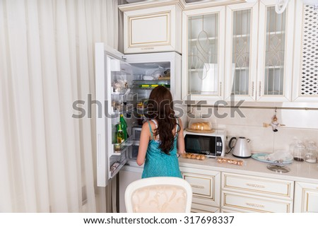 Rear View of Unidentifiable Brunette Woman Standing in front of Open Refrigerator Door in White Kitchen at Home - stock photo