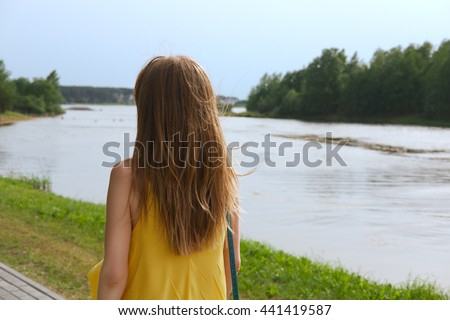 Rear view of walking pretty girl with wind in hair - stock photo