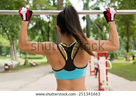 Rear view of woman doing chin-ups on the gym bar - stock photo