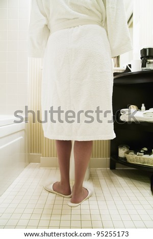 Rear view of woman in bathrobe and slippers - stock photo