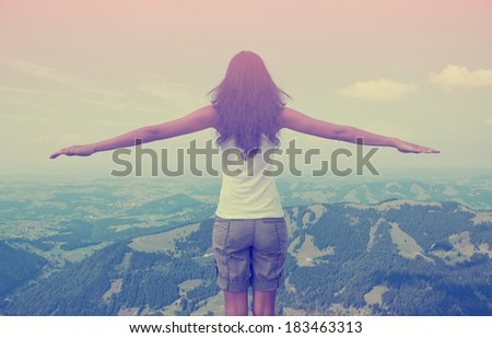 Rear view of woman in nature with arms spreading out - stock photo