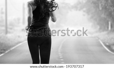 Rear view of woman jogging on the road, black & white tone - stock photo