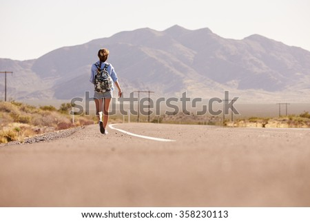Rear View Of Woman On Vacation Hitchhiking Along Road - stock photo