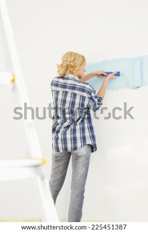 Rear view of woman painting wall with paint roller - stock photo