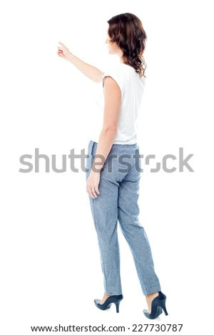 Rear view of woman pointing her finger at something  - stock photo