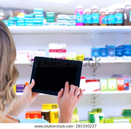 Rear view of woman using tablet pc against close up of shelves of drugs - stock photo