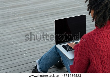 Rear view of young african woman sitting on stairs outdoor and working on laptop. Woman in casual sitting on wooden floors with laptop. Female hands typing on keyboard on her laptop outdoor. - stock photo