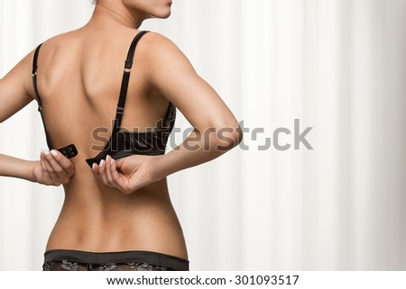 Rear view of young beautiful woman putting on a bra with copy space - stock photo