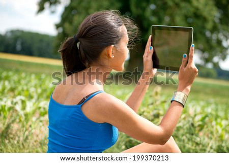 Rear view of young beautiful woman using a tablet sitting on meadow outside in nature - stock photo