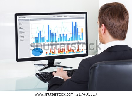 Rear view of young businessman analyzing graphs on computer at desk in office - stock photo
