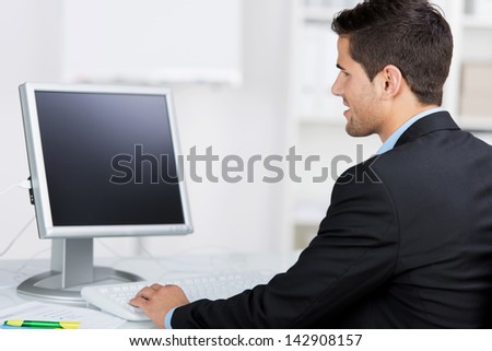 Rear view of young businessman using computer at desk in office - stock photo