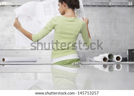 Rear view of young businesswoman reading blueprint at office - stock photo