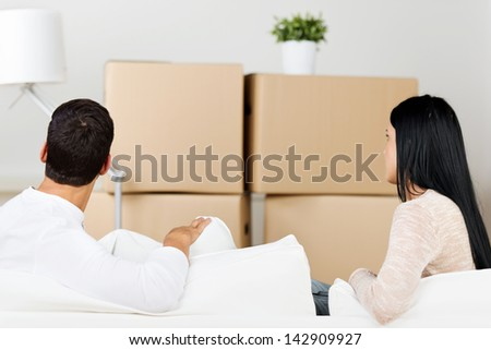Rear view of young couple against cardboard boxes in new house - stock photo
