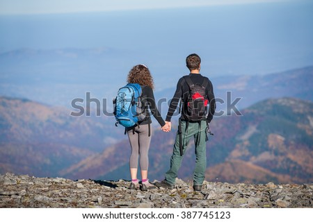 Rear view of young couple hikers with backpacks standing on the ridge of the mountain, enjoying the view of beautiful open overlook on the mountains. Couple is holding hands. Sunny autumn day. - stock photo