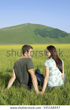 Rear view of young couple looking at each other while sitting together on grassy field at against mountain at park - stock photo