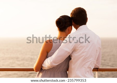 rear view of young couple on cruise vacation looking at the sea - stock photo