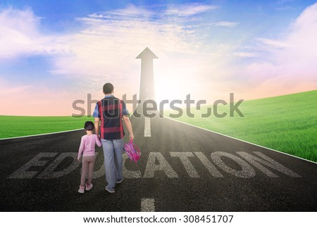 Rear view of young father and his kid walking on the road with education text and upward arrow - stock photo