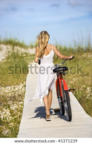 Rear view of young female as she walks her bike down a boardwalk. Vertical shot. - stock photo