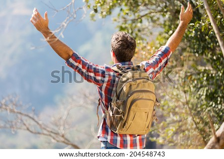rear view of young hiker with arms open on top of the mountain - stock photo