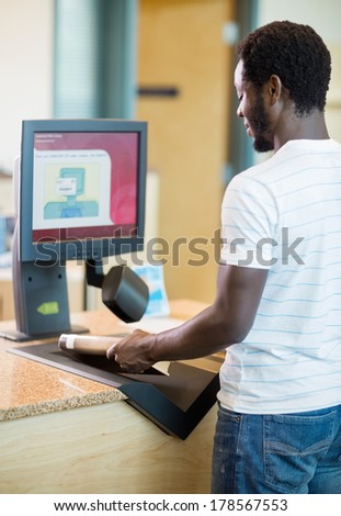 Rear view of young librarian scanning books at counter in bookstore - stock photo