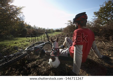 Rear view of young man and dog relaxing beside mountain bike in countryside - stock photo