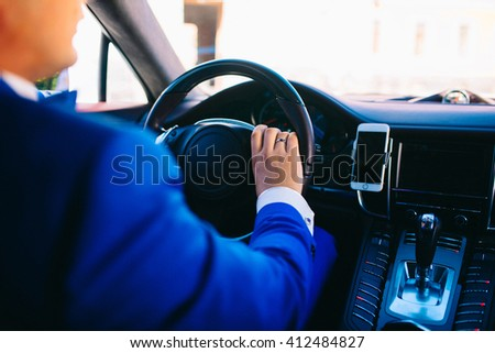 Rear view of young man driving the car. Mount for phone - stock photo