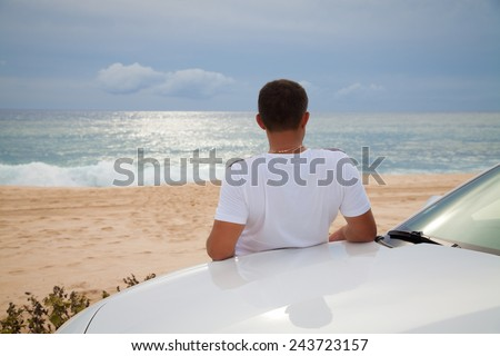 Rear view of young Man leaning on his car parked in front of ocean. Man on road trip enjoying peace and silence relaxing on nature, daydreaming. Vacations And Tourism Concept. Tropical Resort. - stock photo