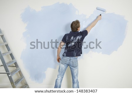 Rear view of young man painting wall with paintroller in unrenovated house - stock photo