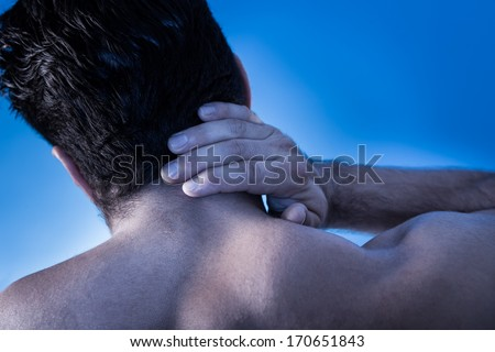 Rear View Of Young Man Suffering From Neck Pain - stock photo