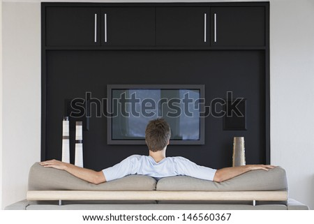 Rear view of young man watching television while sitting on couch in living room - stock photo
