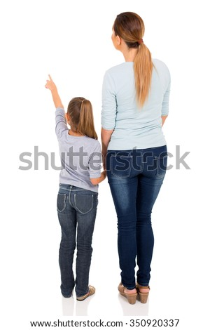 rear view of young mother and daughter pointing at empty space - stock photo
