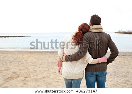 Rear view of young tourist couple with heads together contemplating the sea on sandy beach on a winter holiday, nature outdoors. Cold weather lifestyle. Boyfriend and girlfriend traveling, exterior. - stock photo