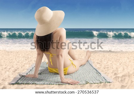Rear view of young woman enjoying summer holiday by sitting at beach while wearing bikini - stock photo