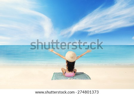 Rear view of young woman sitting on the coast while wearing bikini and enjoy fresh air - stock photo