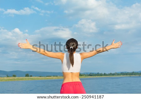 Rear view of young woman standing by the lake spreading arms. Caucasian fitness girl in white and red sportswear with black hair ponytail. Mild retouch, warm tones, vibrant colors, natural light. - stock photo