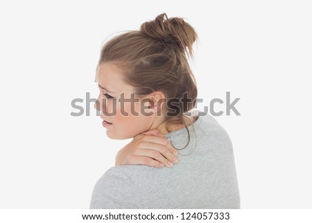 Rear view of young woman suffering from backache over white background - stock photo